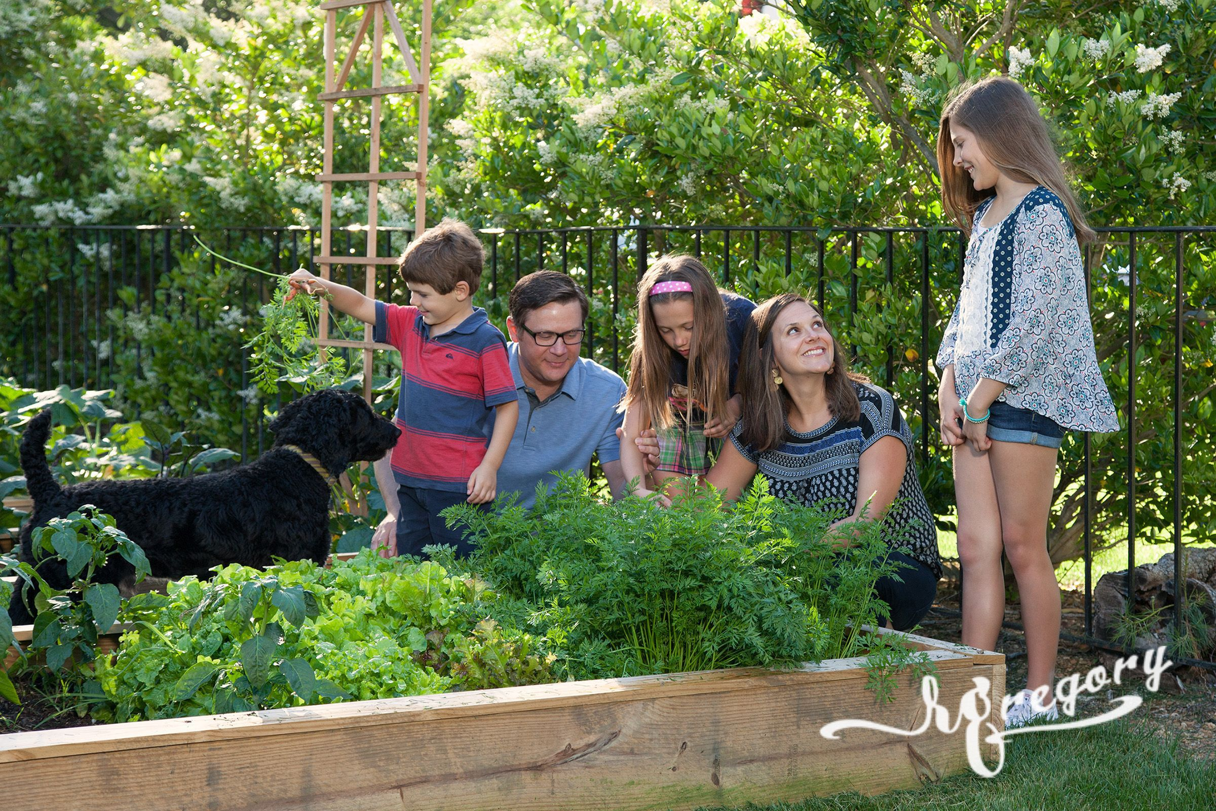 family gardening candid photo with children and pet dog